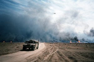An M998 High-Mobility Multipurpose Wheeled Vehicle (HMMWV) drives along a road in the Kuwaiti desert following Operation Desert Storm.  Oil wells set ablaze by retreating Iraqi forces burn in the background.